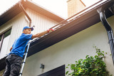 man on ladder cleaning house gutter from leaves and dirt - 208902768