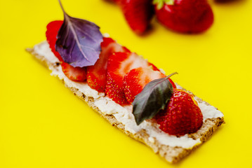 Snack with crispbread, cream cheese, fresh strawberry and basil on a yellow background