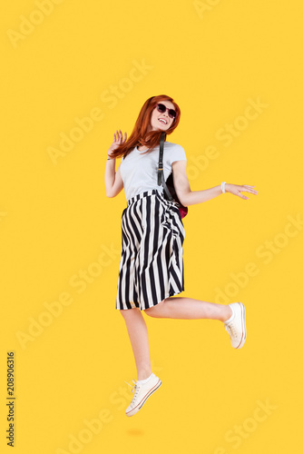 Sticker In motion. Happy nice woman jumping while standing against yellow background