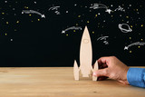 man's hand holding wooden rocket, over black background with space sketch. - 208907106