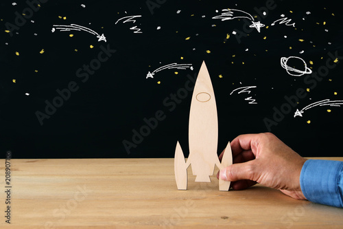 Sticker man's hand holding wooden rocket, over black background with space sketch.