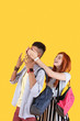 Wonderful mood. Happy nice couple having fun while standing together against yellow background