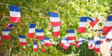 French flags garland decorating a village square - 208910141