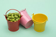 Still life with buckets and green peas on a green background