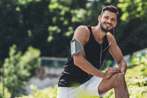Foto Murales smiling sportsman in earphones with smartphone in running armband case doing exercise