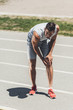 suffering young sportsman receive knee injury on running track