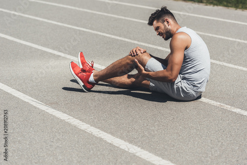 young runner with leg injury sitting on floor of running track