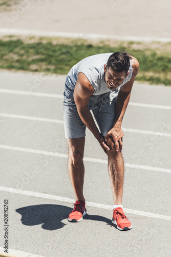 Poster suffering young sportsman receive knee injury on running track