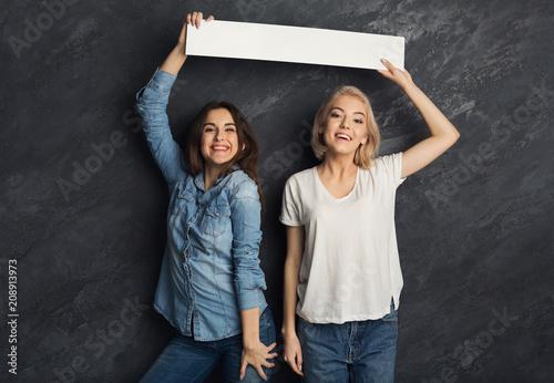 Happy girls with blank white banner at dark studio background