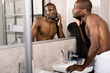 attractive young man examining clarity of skin while looking at mirror in bathroom