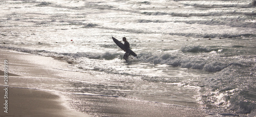 Fototapeta Surfer with surfboard standing