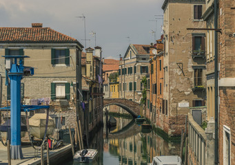 Narrow backstreet canal with bridge and old buildings canalside in Venice, Italy © myowl