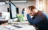 Portrait of overworked employee in modern office