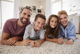 Portrait Of Family Lying On Rug In Lounge At Home - 208925183