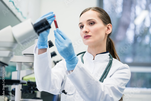 Leinwanddruck Bild Doctor in medical laboratory looking at blood test she is holding in her hand
