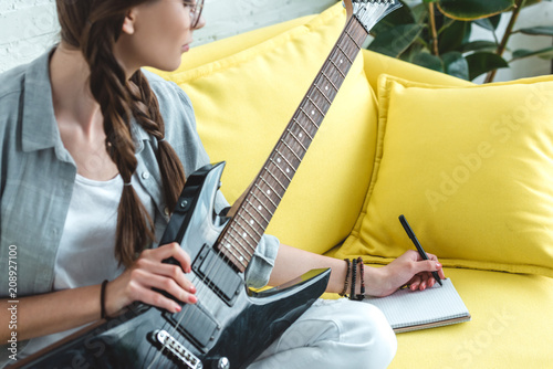 Foto Murales attractive teen girl playing electric guitar and writing song