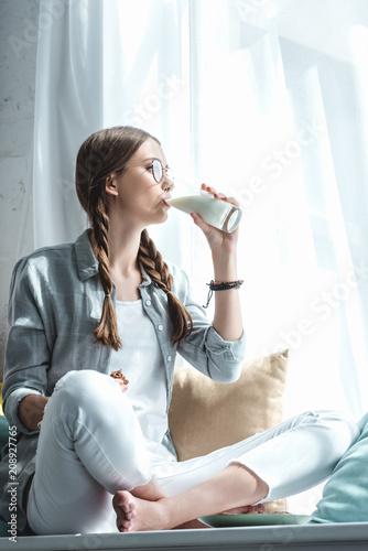 beautiful girl eating cookies and drinking milk on windowsill