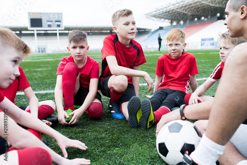 Foto Murales Portrait of group of eager teenage boys sitting in circle listening to motivational pep talk from coach before team practice in outdoor stadium