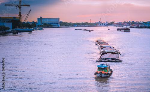 Fotobehang Purper BANGKOK, THAILAND - 2018 JUNE 6: The tug boats towing a big barge with sand. Cargo ship in a river. In Chao Phraya River, Bangkok Thailand under the beautiful sunset sky. Rama VII Bridge in Bangkok.