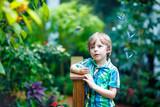 Little blond preschool kid boy discovering flowers and butterflies at botanic garden - 208941364