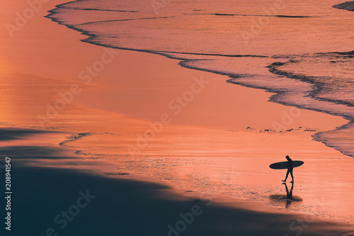 Plexiglas Koraal distant surfer silhouette in the shore at sunset