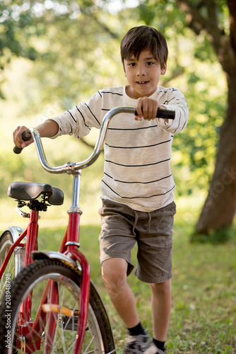 A schoolboy is pleased with a red bicycle in the forest or garden