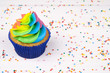 Cupcake with rainbow colorful cream in blue cup on white wooden table decorated with colorful sprinkles.