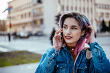 Young woman with dyed hair talking on a phone outdoors.