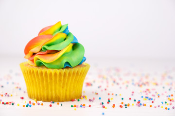 Cupcake with rainbow colorful cream in yellow cup on white wooden table decorated with colorful sprinkles.