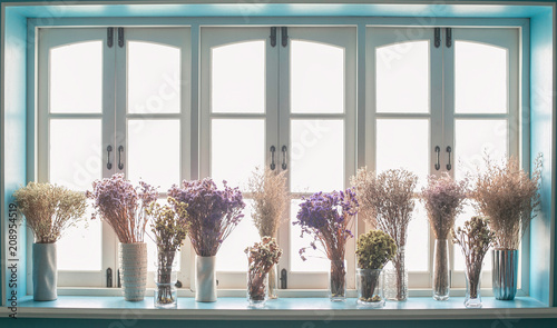 Foto Murales Beautiful flowers in vase with light from window