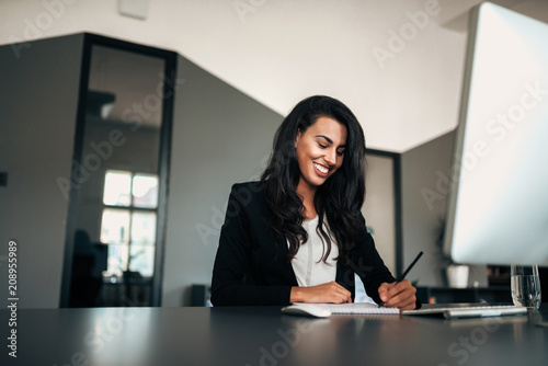 Poster Happy young businesswoman writing in notepad.