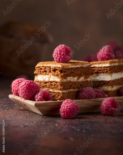 Leinwanddruck Bild Layered honey cake with cream and raspberries.