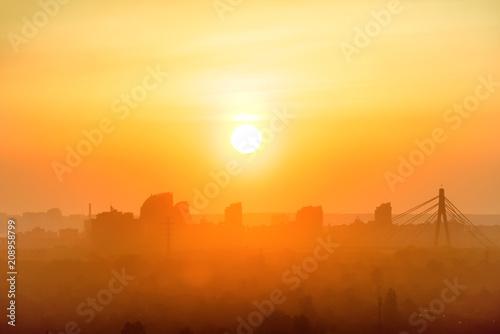 Sunset in the city. Skyline with orange sun on sky