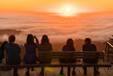 Group of figures watches sunset over clouds filling a forested valley - 208961563