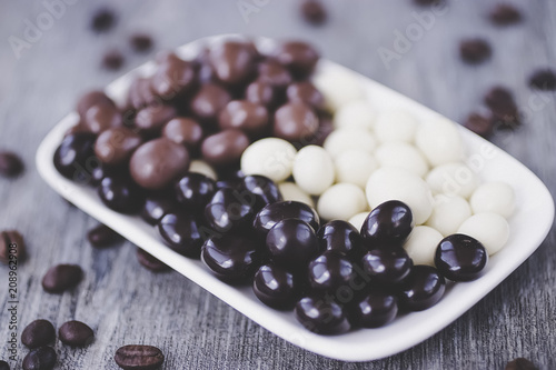 Grains of coffee in glaze of white, milky, and dark chocolate. Gray wooden background.