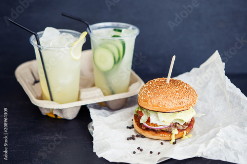 Two beverages and one burger on the black background