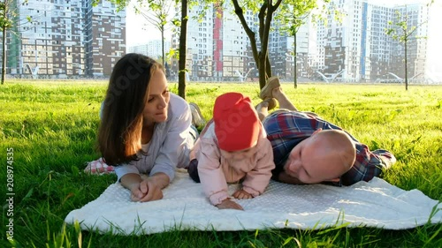 Father and daughter are lying with mother on the grass in the park in the summer. Happy family with little baby resting in summer park at sunset