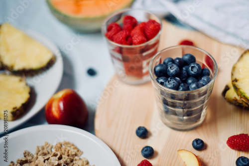 tasty healthy eating vegetarian vegan detox breakfast with fresh seasonal fruits and berries served on chopping board over pastel blue background