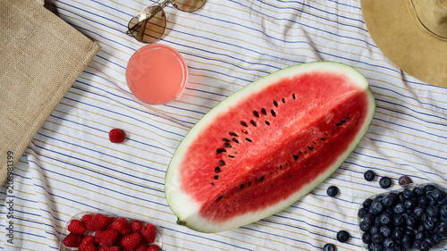 summer picnic setting, outdoor gathering concept, water melon, beach bag, sunglasses, summer hat, fresh seasonal berries and refreshment, refreshing drink on blanket, top view