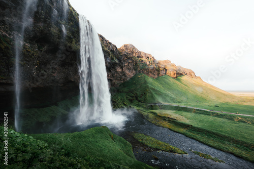 Sunrise on Seljalandfoss waterfall on Seljalandsa river, Iceland, Europe. Amazing view from inside - 208982541