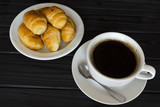 croissants and a cup of coffee on a dark background