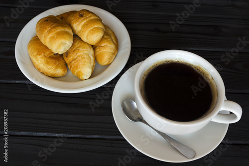 Wall mural croissants and a cup of coffee on a dark background
