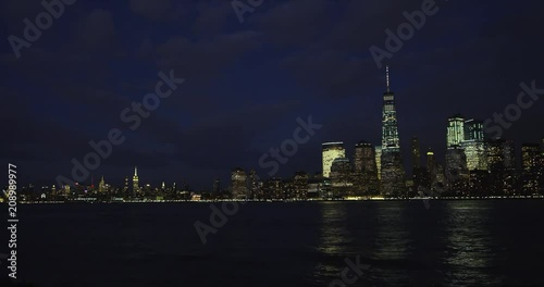 Boats pass New York City skyline time lapse during blue hour