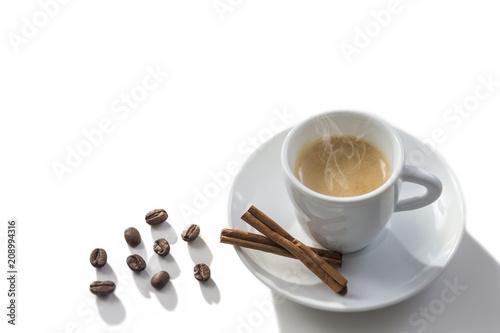 White steamy cup near cinnamon sticks in coffee beans, whitebackground