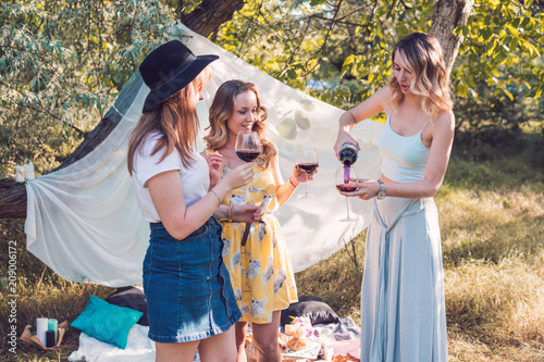 Group of girls friends making picnic outdoor. They they pour wine from a bottle into glasses.
