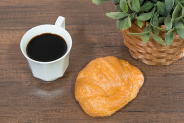 Freshly baked homemade croissants and black coffee on wooden cutting board, top view