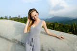 Young relaxed female person standing in mountains background, wearing grey shirt. Concept of nature and traveling, summer vacations. - 209011738