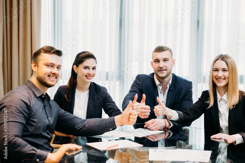 success and financial achievement concept. confident business men and women giving thumbs up.