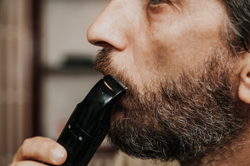 Cutting mustache with black trimmer close-up