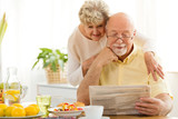 Senior couple reading newspaper during morning breakfast - 209023751